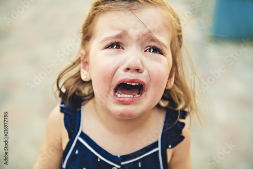 Foto Close up portrait of crying little toddler girl with outdoors background