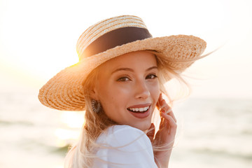 Obraz Cute blonde woman wearing hat outdoors at the beach