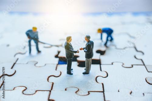 Fotografia  Miniature on wood jigsaw, Business concept
