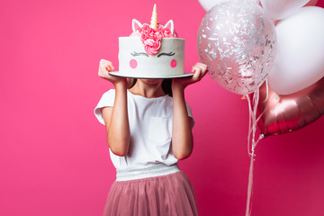 girl with a cake for a birthday, in the Studio on a pink background, festive mood, close - up, designer cake