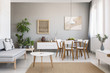 Leinwanddruck Bild - Real photo of a spacious dining and living room interior with wooden furniture and plants on a pedestal
