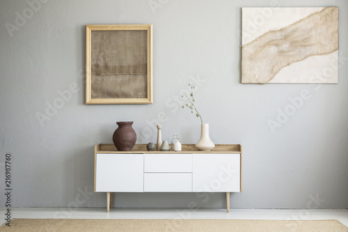 Valokuva  Front view of burlap artworks on a light gray wall above a wooden cupboard with