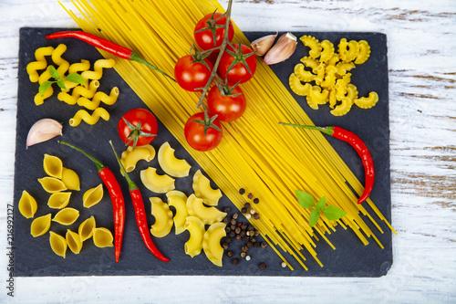 Raw pasta, chili, tomatoes and basil