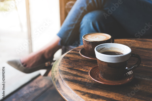 Papiers peints Cafe Closeup image of two cups of hot latte coffee on vintage wooden table with woman sitting in background