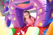 canvas print picture - A cheerful child plays in an inflatable castle