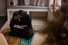 Muslim Mother Assisting Her Da...