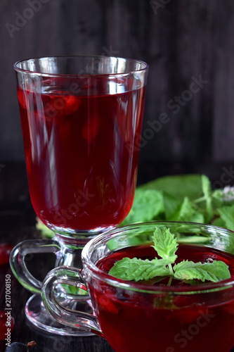 Berry kissel in a glass cup and in a mug against the dark background