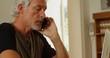 Senior man talking on mobile phone at home 4k
