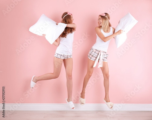 Fotografía  Two young women having pillow fight near color wall