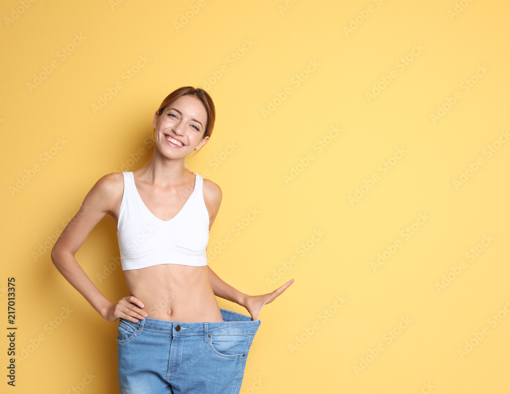 Fototapety, obrazy: Young slim woman in old big jeans showing her diet results on color background