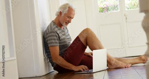 Senior man using laptop at home 4k