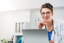 Portrait Of Woman Doctor At Her Medical Office Writing Prescription
