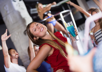 Woman dancing in the night club with drinks