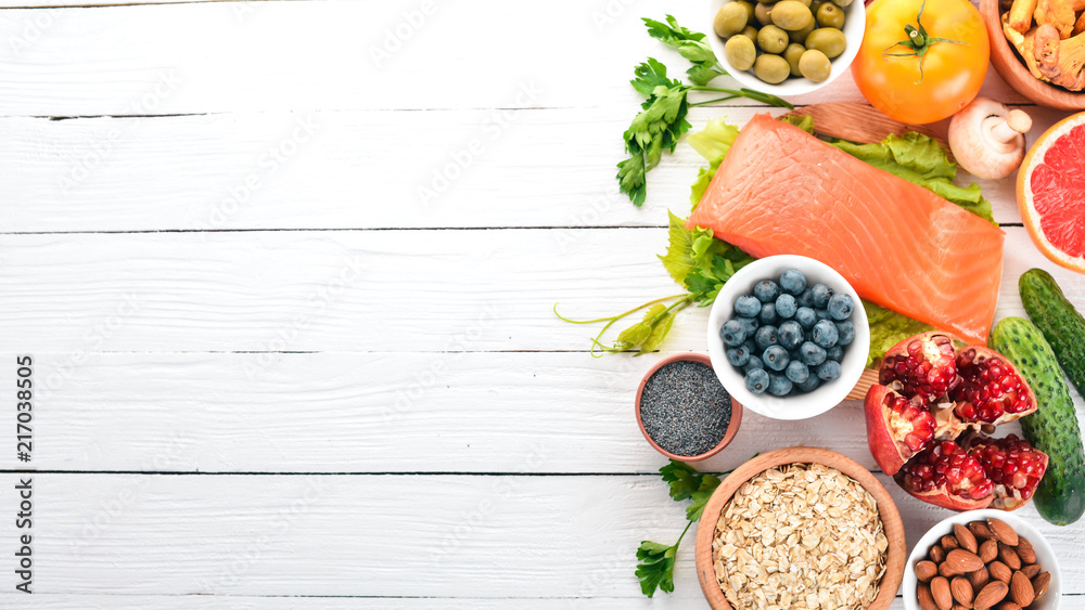 Fototapety, obrazy: A set of healthy food. Fish, nuts, protein, berries, vegetables and fruits. On a white background. Top view. Free space for text.