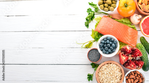 A set of healthy food. Fish, nuts, protein, berries, vegetables and fruits. On a white background. Top view. Free space for text.