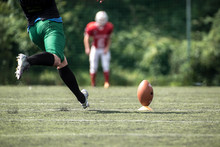 American Football Player Kicking Ball