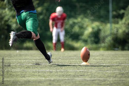 Fotografija American football player kicking ball