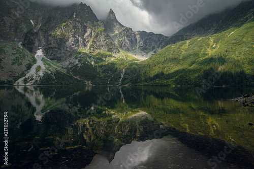 Poster Bergen Scenic view of green forest, hills ang rocky cliffs with reflection on the Morskie Oko lake, High Tatras, Zakopane, Poland