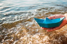 Girl Holds A Blue Paper Boat In The Hands On A Blue Sea Background. Summer By The Sea