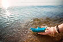 Girl Holds A Blue Paper Boat I...