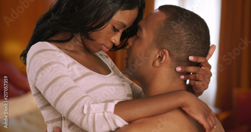 Intimate African couple showing affection privately in bedroom Wallpaper Mural