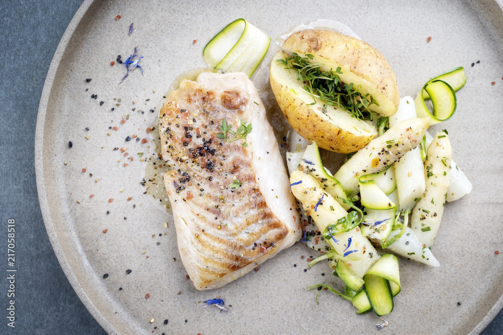Fototapeta Modern German fried cod fish filet with white asparagus tips and roast potatoes as top view on a plate