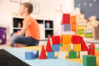 canvas print picture - Castle made from cubes and little boy with autistic disorder on background