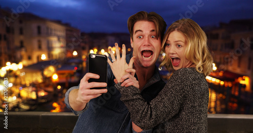 Fotografie, Obraz Newly engaged couple taking a selfie by the Grand Canal at night