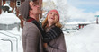 Happy Caucasian couple enjoying winter day in the snow smiling and laughing