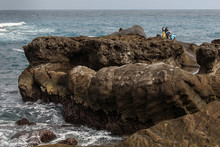 Coral Reef Formations With Crashing Turbulent Blue Ocean Waves In The Foreground. Taiwan East Coast Rocky Coastline Background Image - Overcast Skies, Exotic Rock Formations, Fishermen
