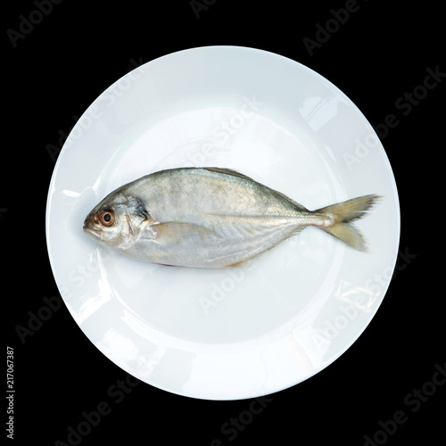 Fotografija  Yellow Tail Scad fish, Decapterus fish, on White plate, isolated on black backgr
