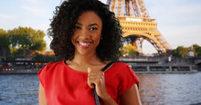 Happy Black Woman Smiling By The River Seine With A View Of The Eiffel Tower In Paris