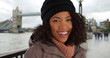 Happy black woman smiling in front of Tower Bridge wearing jacket and beanie