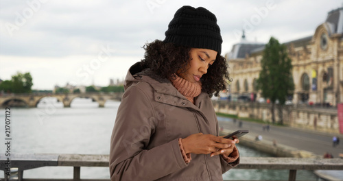 African American woman using smartphone to check direction while in Paris фототапет