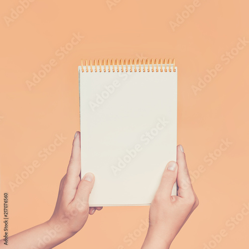 Female hands holding open a blank Notepad for notes on the peach background. Toned.