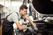 Car service and maintenance: an automechanic is repairing a vehicle