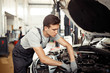 A qualified automachanic is repairing a car at a car service