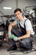 A young and qulified car mechanic is sitting at a car service
