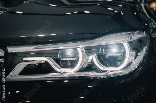 Fototapeta  Closeup headlights of modern car during turn on light in night.