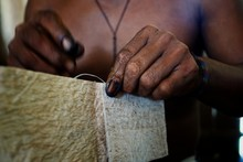 Ticuna Indian Tribal Member Stitching A Tree Bark Artifact Together
