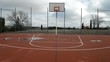 Empty outdoor basketball court with puddles on the floor. You can see a basketball hoop and the lines drawn on the court.
