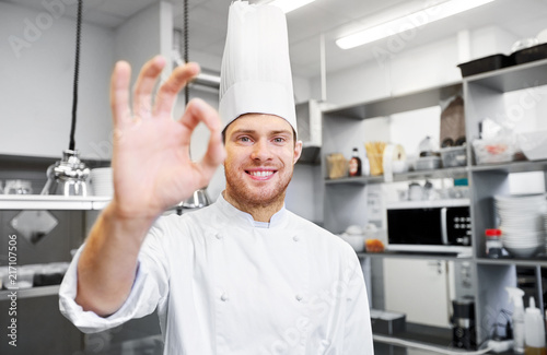 Photo cooking, profession and people concept - happy male chef cook in toque at restau