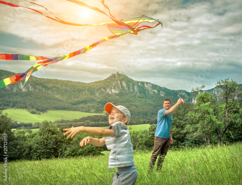 Fotografie, Obraz  Happiness father and son launch a kite to blue sky on the field