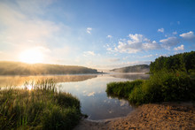 Foggy Lakeside At Sunrise With Tall Grass And Sand In Foreground