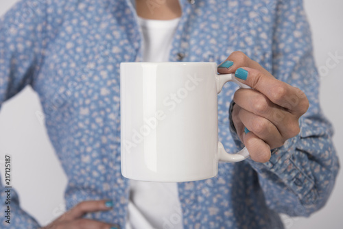 Hand Holding White coffee cup. mockup for creative design branding.