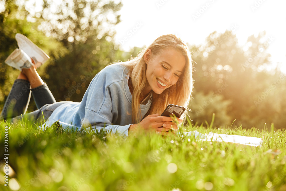 Fototapeta Portrait of a cute young girl laying on a grass at the park