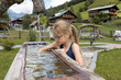 ein 7 jähriges Mädchen tauchen ihre Hände in das kalte Wasser eines Armbads nach Kneipp