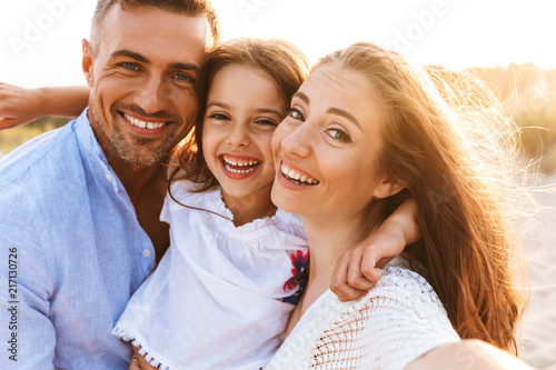 Obraz Parents having fun together outdoors at the beach with their daughter. - fototapety do salonu