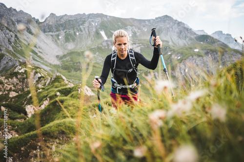 Obraz na plátně Adventurous Sportive Girl hiking in Beautiful Alpine Mountains