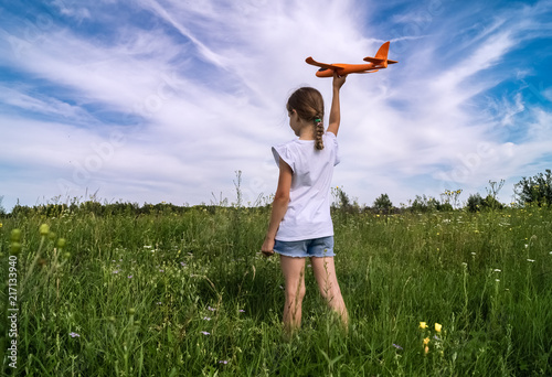 A baby girl is launching a toy airframe glider in a field against a blue sky background with clouds Wallpaper Mural